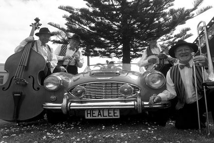 Jazz players with instruments pose by a car with the number plate Healee