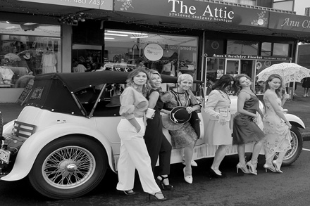 Gorgeous gals in vintage fashion pose near a vintage car